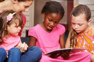 Kinder lernen lesen mit Erzieherin